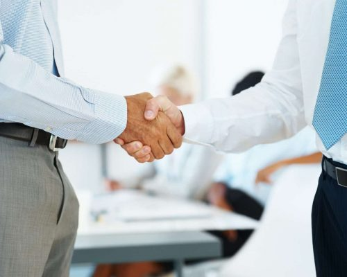 Two business man shaking their hands in office - Corporate deal